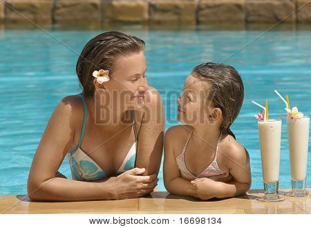 Woman and girl in the swimming pool with cocktail