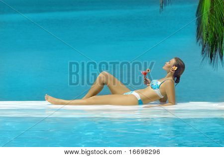 woman in the swimming pool with cocktail