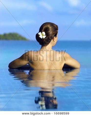 Woman  in the swimming pool near the ocean