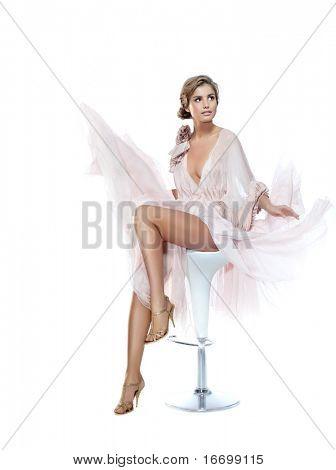 attraktive lächelnde Frau in rosa Kleid auf weißem Hintergrund