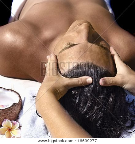 man's massage close up with coconut and flowers