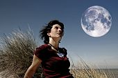 picture of positive thought  - girl staring at the full moon and sitting near the sea - JPG