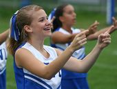 stock photo of cheerleader  - Youth Cheerleader Cheering at Game with squad on sidelines - JPG