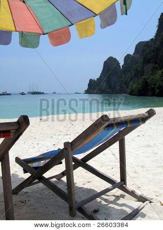 Sun chair under umbrella on a tropical sandy beach of Phi-Phi island