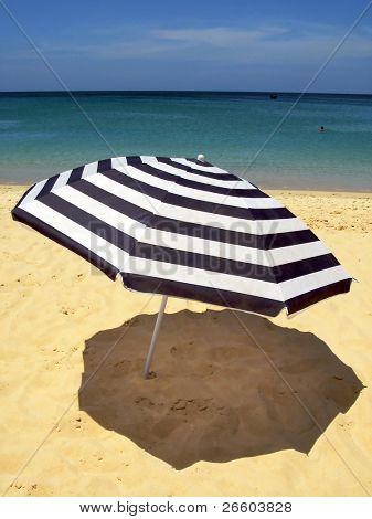 Striped umbrella against sandy beach and ocean