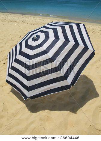 Striped umbrella on a sandy beach
