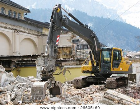 Excavator demolishing an old building