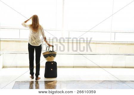 Menina na janela do Aeroporto, olhando para o Oceano