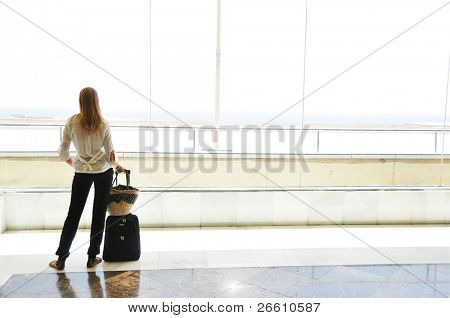 Girl at the airport window looking to the ocean