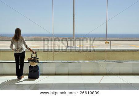 Muchacha en la ventana de aeropuerto mirando al océano