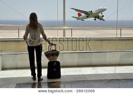 Muchacha en la ventana de aeropuerto