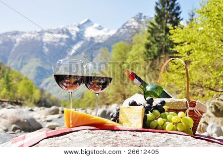 Red wine, cheese and grapes served at a picnic. Verzasca valley, Switzerland