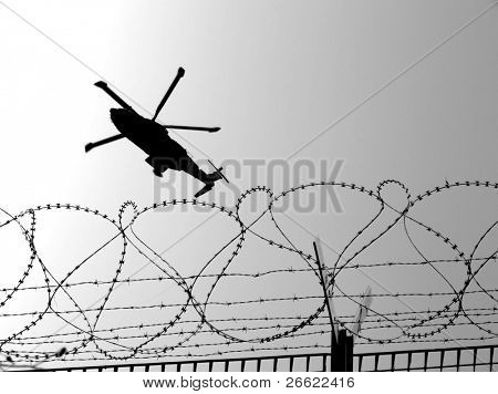 Barbwire and military helicopter in mission of war