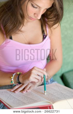 Girl student consults analytic index of an university book that is studying