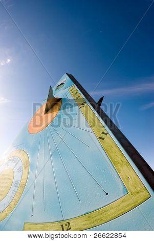 Pyramidal sundial on the background of shading blue sky