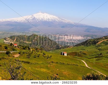 Rural road and hilly landscape of the territory of the volcano Etna snow covered