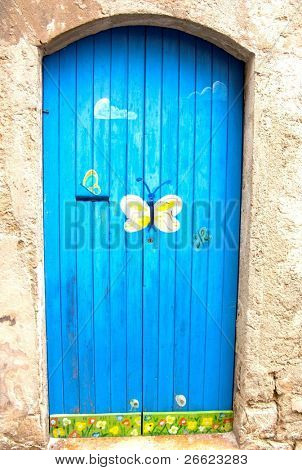 picturesque blue door with painted butterfly of a home