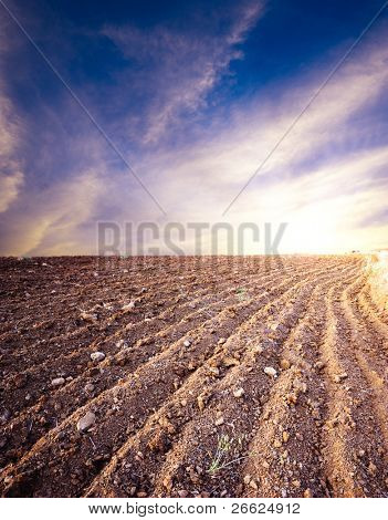 plowed land on background cloudy sky