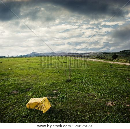 yellow plastic box abandoned in desolate grass area
