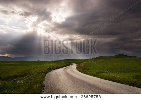 road crosses prairie covered by clouds into rays of sun