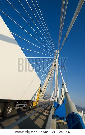 A truck through the pylons of suspension of a bridge. You can use the side of trucks to insert a text