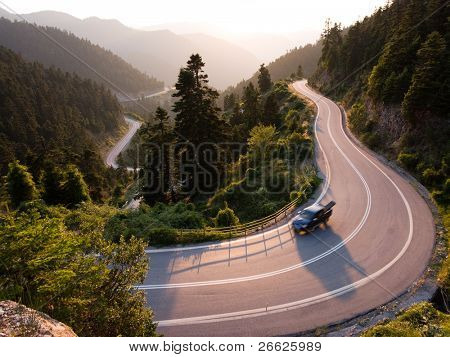 pickup crosses mountain road winding in twilight