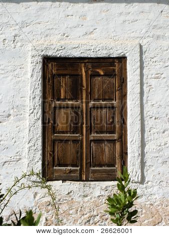 A window of wood closed on the wall of a house Greek with the walls plastered with lime white