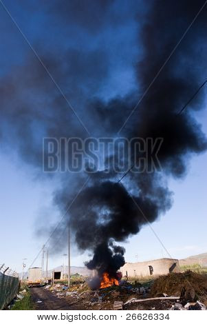 In a region sub-urban town of Adrano in Sicily was created an illegal landfill site where they have destroyed by fire of awnings of car and is lifted a long column of black smoke