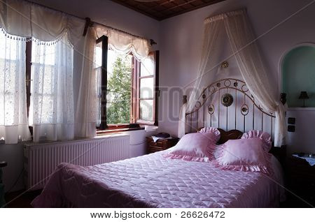 Two brightly-lit window in a old style romantic bed room