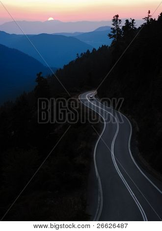 car traveling winding road between mountain at sunset