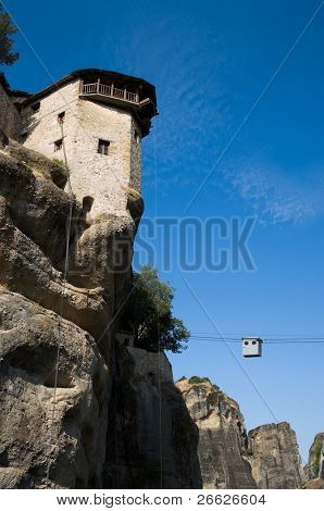 view of a monastery tower on top of a pinnacle - Meteora in Greece - and cableway to transport people and things