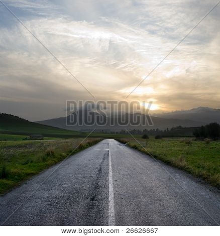 straight road crosses a desolate country road at the gloomy sunset