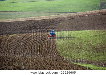 a blue tractor with a plow furrows the earth