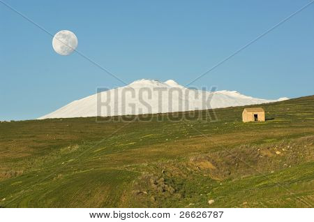 green slope with a shack and mount Etna covered by snow under the full moon in the blue sky of evening