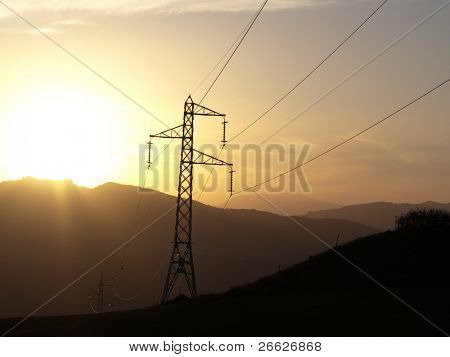 silhouette of electricity pylon and cables at the sunset on the ridge of mountains