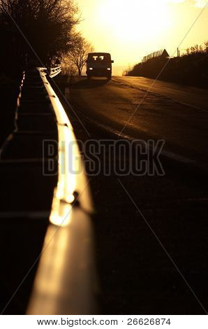 vanish guardrail and front view of car with their lights on in the sunset