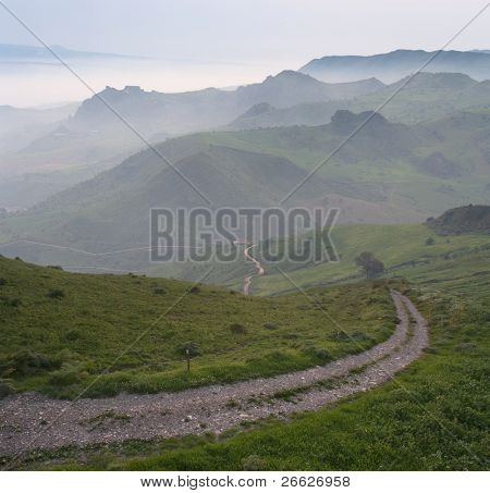a curve dirt road and layered hillside grassland in the mist