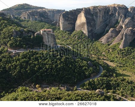 winding road crosses the landscape of the Meteora to go to the Roussanou monastery