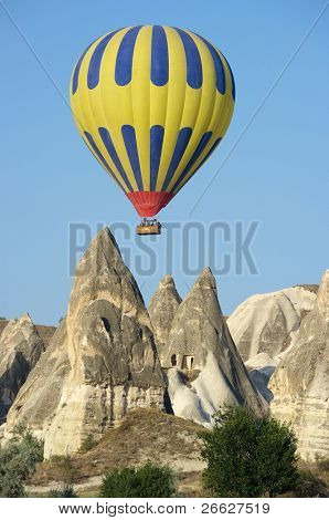 balloon over fairy chimneys, typical rock formation in Goreme, Turkey