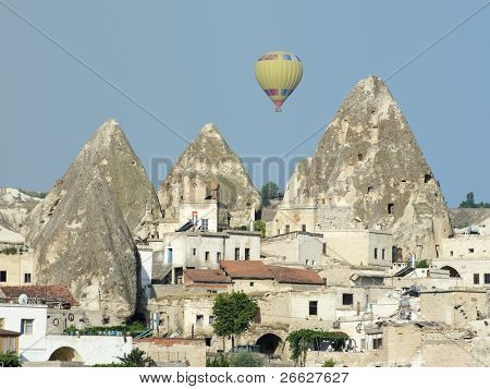 a hot air balloon over the fairy chimneys and houses in village Goreme, Cappadocia, Turkey