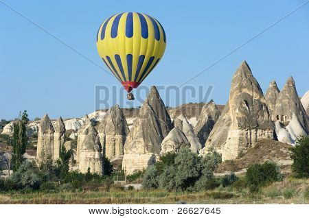 balloon over fairy chimneys, typical rock formation in Cappadocia, Turkey