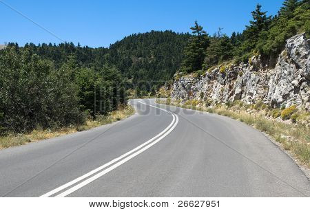 winding road mountain crosses fir woods under the blue clear sky