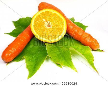 Cenouras e fatia de laranja em folhas verdes