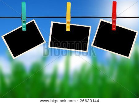 Blank photos hanged on peg with sky and grass background