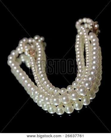 Pearl necklace, reflected on black background