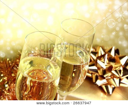 Champagne glasses with golden gifts on shiny blur background