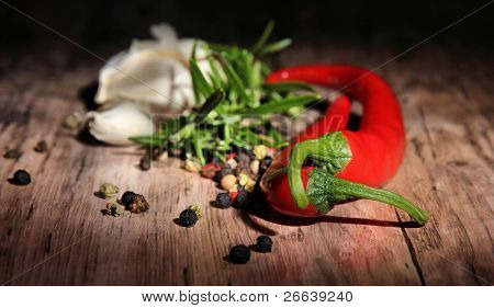 Red hot chili peppers with spice ingredients over wooden background