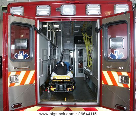 Paramedic's truck with open back doors, where stretcher and medical equipment is visible. All trademarks, names and identifications removed.