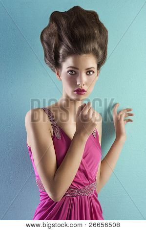 Young Pretty Model Dressed In Pink And With Haute Couture Hair Style