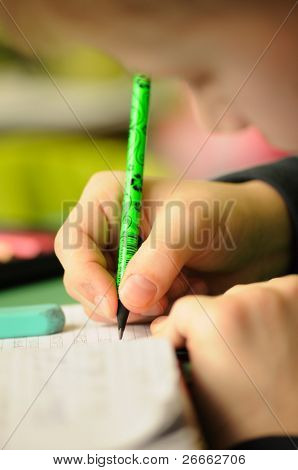 Kid in classroom with pen in hand